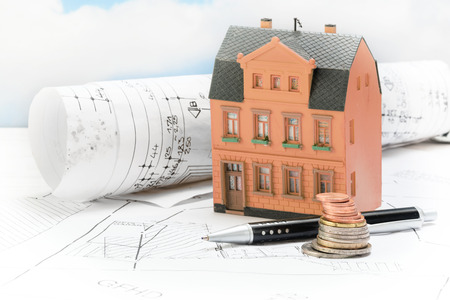 Investment in old building renovation, model house with architectural plans, coins and pen, real estate concept with copy space, selected focus Reklamní fotografie