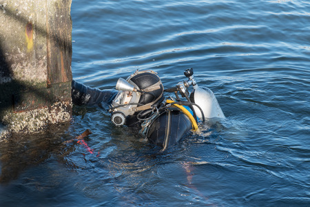 industrial diver with scuba gear, diving helmet and protective suit working in the water at the shore reinforcement, copy space