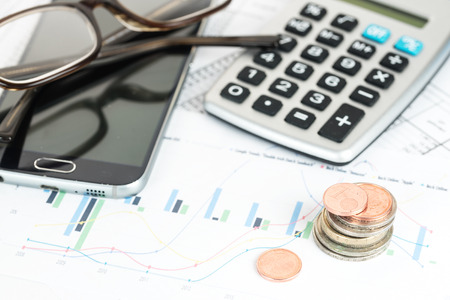 stack of euro coins, calcualtor, phone and glasses on a financial report, business concept for finance, economy, pension and poverty, close up with selected focus, narrow depth of field