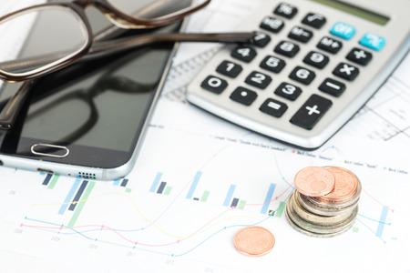 Stapel euromunten, rekenmachine, telefoon en bril op een financieel rapport, bedrijfsconcept voor financiën, economie, pensioen en armoede, close-up met geselecteerde focus, smalle scherptediepte Stockfoto - 96103637