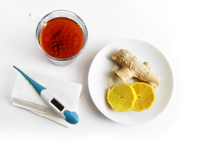 hot tea, a plate with lemon and ginger and a medical thermometer on paper tissues, health concept against cold and flu on a light background with copy space, high angle view from above