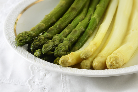 cooked asparagus, green and white on a plate, white table cloth, closeup, selective focus, narrow depth of field Stock Photo