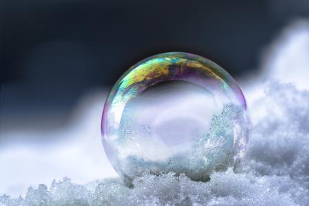 Bulle de savon avec reflets arc-en-ciel dans la neige, nature morte d'hiver avec fond sombre et espace copie, mise au point sélectionnée