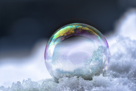 soap bubble with rainbow reflections in the snow, winter still life with dark background and copy space, selected focus