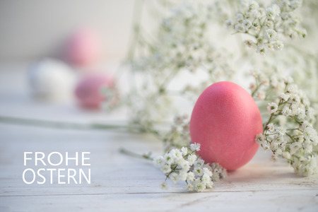 pink egg and gypsophila (baby breath flower) on white painted rustic wood , german text Frohe Ostern (Happy Easter), selected focus, narrow depth of field
