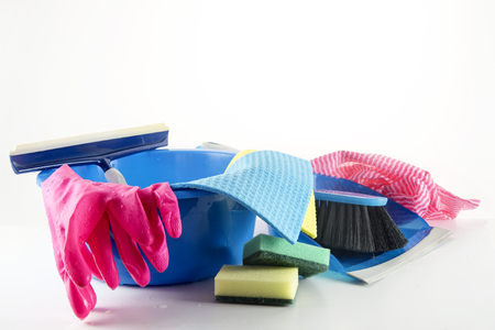 spring cleaning household tools, plastic bowl with rubber gloves, glass wiper and cleaning rags, dustpan, brush, and sponges on a light gray background fading to white, copy space, selected focus