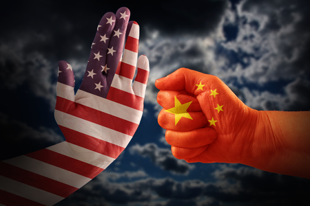 Trade conflict, USA flag on a stop hand and China flag on a fist against a dramatic cloudy sky
