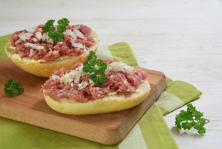 Bread rolls with minced pork sausage, german zwiebelmettwurst with onions and parsley garnish on a breakfast board,  green napkin and white wooden background with copy space