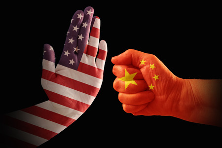 Trade conflict, USA flag on a stop hand and China flag on a fist, isolated against a black background