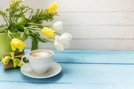 coffee cup, yellow and white tulip flowers in a green vase and a little gift on turquoise wood, white wooden background with copy space,  selected soft focus, narrow depth of field Banco de Imagens