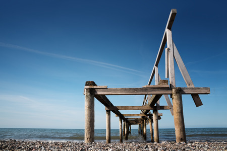 Broken wooden pier or jetty leads into the sea against a blue sky, perspective from below, copy space Stock Photo