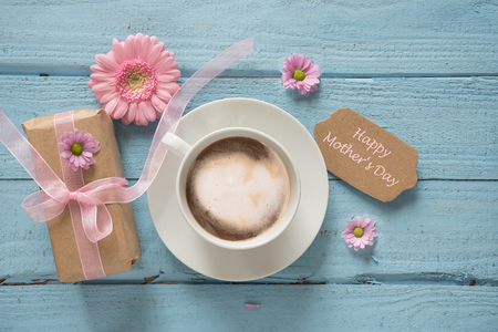 Coffee cup, pink flowers and a gift on pastel blue wood background with copy space, text Happy Mother's Day, top view from above
