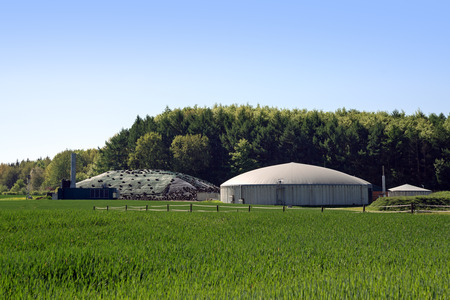 biogas plant for renewable energy in a field in front of a forest, blue sky, copy space, selected focus Stock Photo