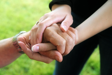 young womens hands hold the hand of a elderly, selected soft focus, narrow depth of field