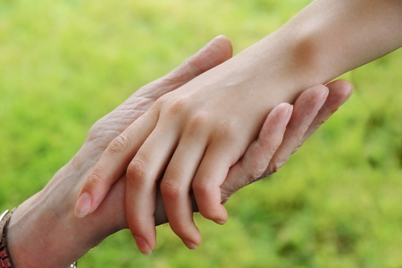 seniors hand holds the hand of a young woman, aid concept, green background, selected soft focus, narrow depth of field Banco de Imagens