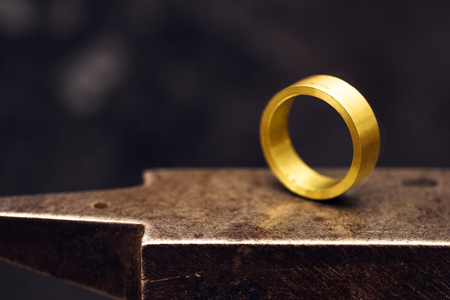 Golden ring on a goldsmith anvil in the jewelry factory, close up shot with copy space in the dark background, selected focus, narrow depth of field