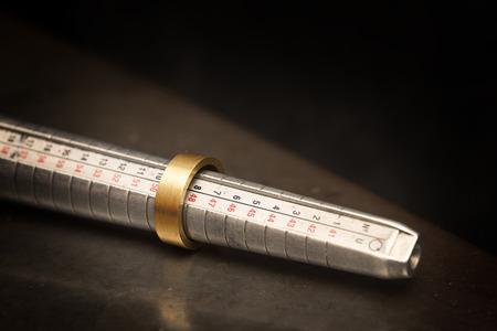 Gouden ring op een ringmaatmeter, juweliersmaatgereedschap van staal tegen een donkere achtergrond met kopie ruimte, geselecteerde focus, smalle scherptediepte