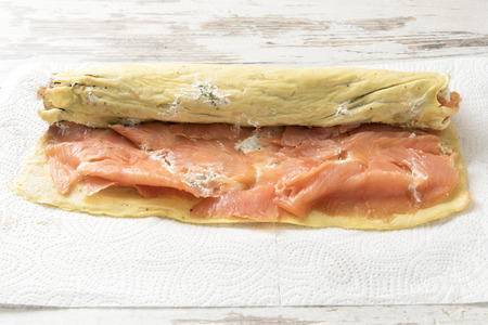 pancake roll with smoked salmon, cream cheese and herbs on a wooden kitchen table, copy space, selected focus, narrow depth of field Stock Photo
