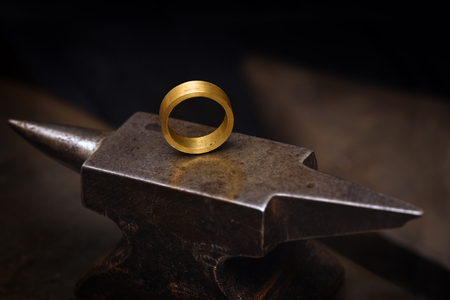ring from gold on a goldsmith anvil in the jewelry manufactory, still life with copy space in the dark background, selected focus, narrow depth of field Archivio Fotografico - 107279032