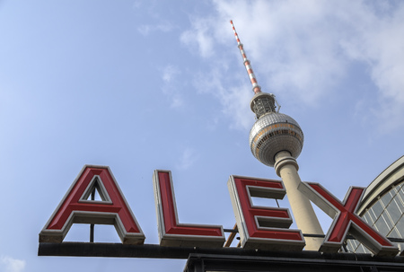 neon sign from alexanderplatz, also called alex with the famous television tower against the blue sky in berlin the capital city of germany, copy space