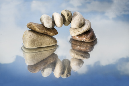 arch, bridge or gate made of balanced pebbles with reflection in the water, blue sky with clouds, copy space