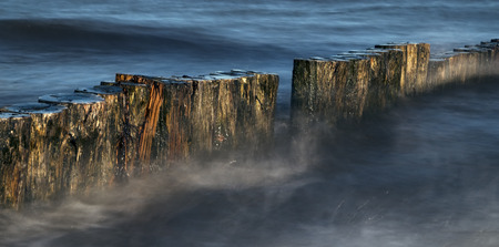 wooden groynes in the blue sea, smooth water by long exposure, nature background with copy space in panoramic banner format Standard-Bild - 109750171