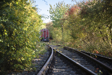 old railway wagon parked on the tracks in the bushes Editorial
