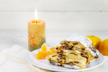 Christmas cake, german christstollen with tangerines and a burning candle against a white wooden