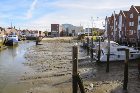 Husum inland port at low tide with slipway and boats on the mudflat on a sunny day