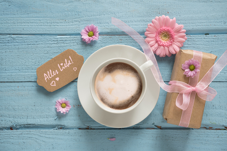 Coffee cup, pink flowers and a gift on pastel blue wood