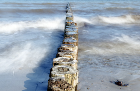 Wooden groynes as coast protection in the sea on a sunny day Standard-Bild - 113136751