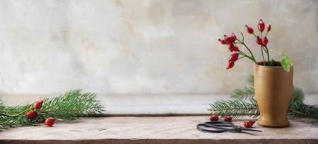 Rosehips and fir branches in a stoneware vase and on a rustic wooden table Foto de archivo