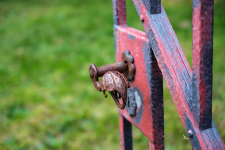 Wrought iron handle at an open old garden gate with worn red color
