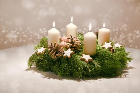 Vierter Advent - geschmückter Adventskranz aus Tannen- und immergrünen Zweigen mit weißen brennenden Kerzen