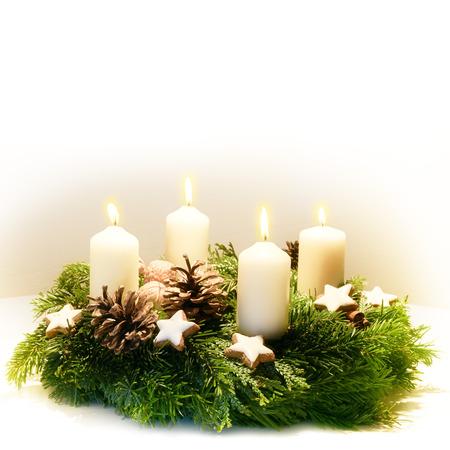 Geschmückter Adventskranz aus Tannen- und immergrünen Zweigen mit brennenden weißen Kerzen Standard-Bild