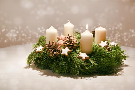 Erster Advent - geschmückter Adventskranz aus Tannen- und immergrünen Zweigen mit weißen brennenden Kerzen Standard-Bild