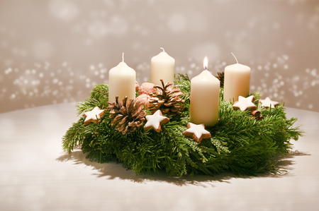 First Advent - decorated Advent wreath from fir and evergreen branches with white burning candles