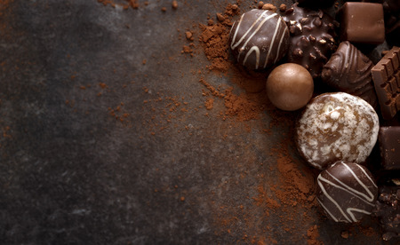 chocolate cookies and pralines on a dark stone slab with large copy space, high angle view from above Stockfoto