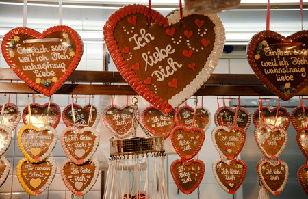 gingerbread hearts hanging in a candy stand at the christmas market, German text Ich liebe Dich, meaning I love you