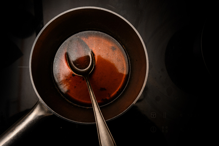 Pot and spoon with beef stock while cooking a red wine morel sauce on a black stove