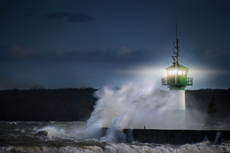 Lighthouse during storm in splashing spray  at night on the Baltic Sea Stockfoto