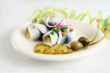 Rollmops or rolled pickled herring with red onions