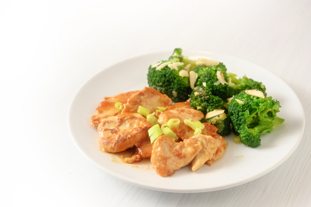 marinated chicken breast fillet with spring onions and broccoli with almond sticks as a healthy meal with little carbohydrates for slimming on a plate, background is blending to white, copy space, selected focus, narrow depth of field Banque d'images