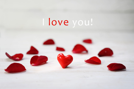 red glass heart between rose petals on a light grey wooden background, text I love you, selected focus, narrow depth of field