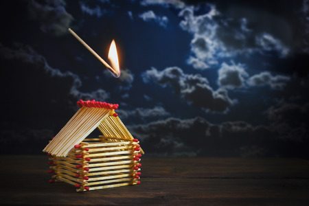 inflamed match is falling on a house built of matches against a dark stormy sky with copy space, insurance concept for danger or financial risk in real estate investment, selected focus, narrow depth of field