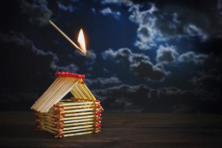 match enflammé tombe sur une maison construite d'allumettes contre un ciel orageux sombre avec espace de copie, concept d'assurance pour le danger ou le risque financier dans l'investissement immobilier, mise au point sélectionnée, faible profondeur de champ Banque d'images