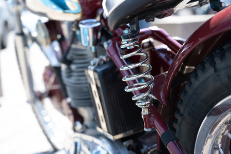 Chrome plated shock absorber spiral spring under the saddle of a red classic motorcycle, selected focus, narrow depth of field