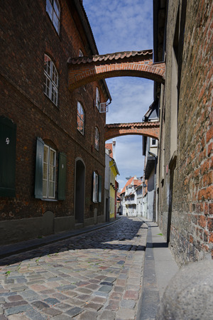 Narrow cobblestone street with arches between the historic houses in the old town of Luebeck, famous tourist destination in Schleswig-Holstein, Germany 스톡 콘텐츠