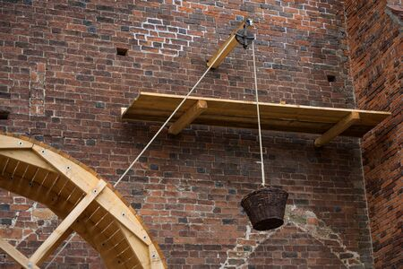 treadwheel crane, pulley and a hanging basket for heavy charge as demonstration of historical construction techniques on the brick wall of an old church