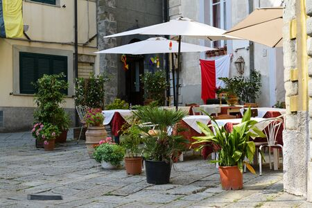 Street cafe or restaurant with decorated tables and flowerpots in the old town of Fivizzano, a small Lunigiana city in the province of Massa and Carrara, Tuscany, Italy